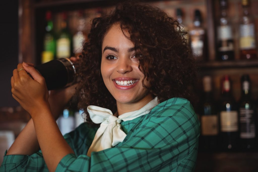 Female bartender mixing a cocktail drink in cocktail shaker