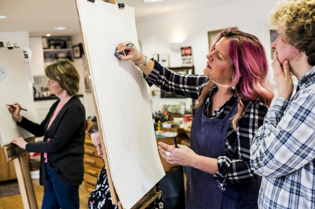 Woman standing at an easel, drawing a human leg at a life drawing glass.
